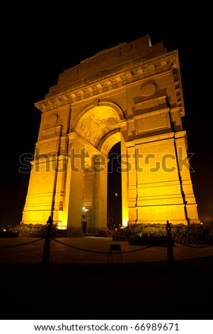 The moon is visible through the India Gate memorial beautifully illuminated at night in central Delhi, India - stock photo