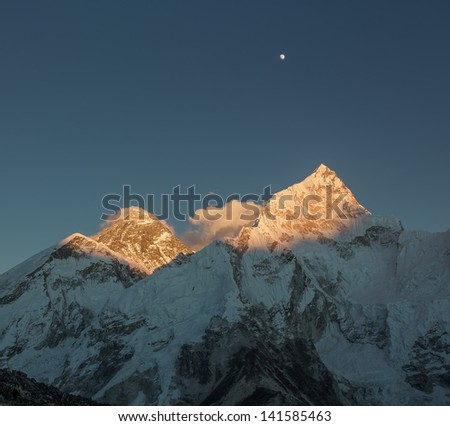 The Moon, mount Everest (8848 m), and Nuptse (7864 m) in the evening (view from Kala Patthar) - Nepal, Himalayas - stock photo
