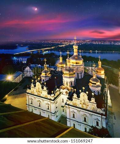 The moon on the crimson dawn sky hangs over the ancient temples of the main Christian shrines of Ukraine - stock photo