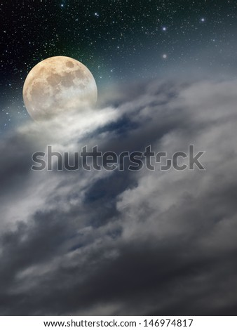 The moon rises over a region covered with clouds - stock photo
