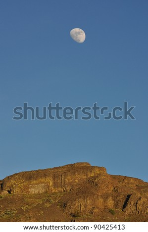 the moon rises over the mountain top - stock photo