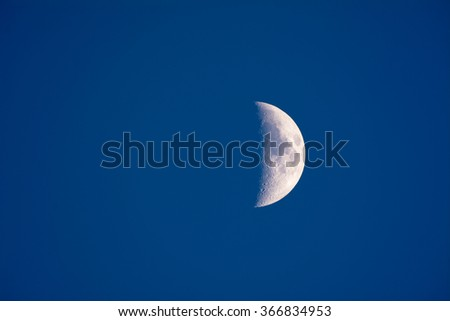 The moon shot just before dark shows a partial planet and blue atmosphere. - stock photo