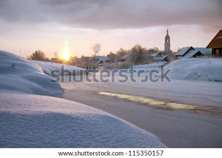 The morning sun illuminates the frozen river in winter - stock photo