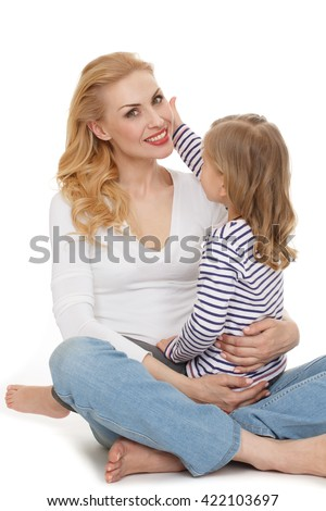The most beautiful. Vertical shot of a little girl sitting on her mothers lap touching her face isolated on white. - stock photo