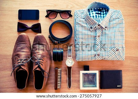 The most important things. Top view of clothing and diverse personal accessory laying on the wooden grain - stock photo