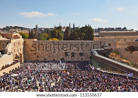 The most joyful holiday of the Jewish people - Sukkot. The Western Wall of the Jerusalem temple. The area before it is filled up by people on time of a morning prayer - stock photo