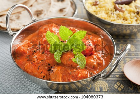 The most popular curry in the UK, chicken tikka masala, here served in a balti dish or karahi, garnished with mint, accompanied by pilau rice and chapatis. - stock photo