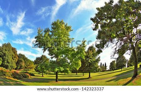 The most romantic landscape park garden in Italy. Lovely green grassy lawn at sunset.  Photo taken fisheye lens - stock photo