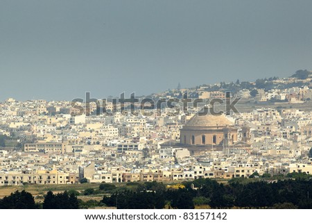 The Mosta Dome is said to be the third largest in Europe, and can be seen here dominating over other modern buildings in the vicinity - stock photo