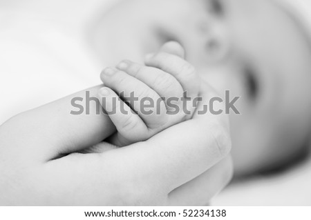 the mother holds hand of her baby - stock photo