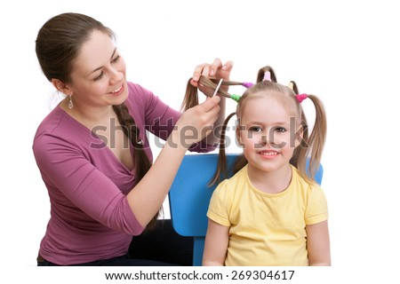 The mother makes her little daughter a beautiful hairstyle - stock photo