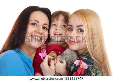 The mother stands with her two daughters hugging on white isolated background - stock photo
