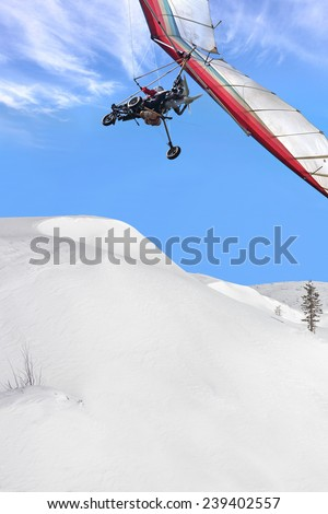 The motorized hang glider above Winter snow covered mountain - stock photo