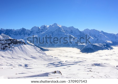 The mountain ridge of Mont Blanc seen from the north side. Blue sky, untouched snow fields in front and a valley full of clouds. - stock photo