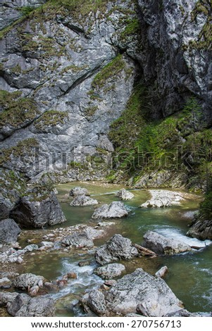 The mountain river with boulders at the foot of the cliff. It is in the Carpathian Mountains, Romania, Transylvania. - stock photo