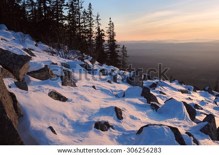 The mountain slope with stones are covered by snow in the winter evening light on the backdrop of the hazy distance, Sinyak mountain, South Urals, Russia. - stock photo
