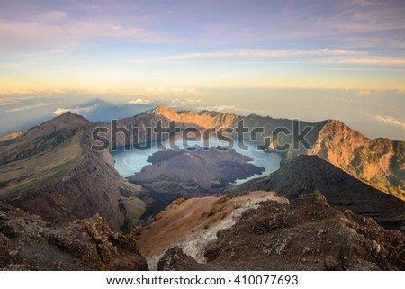 The Mt. Rinjani crater and a shadow cast from the peak at sunrise - stock photo