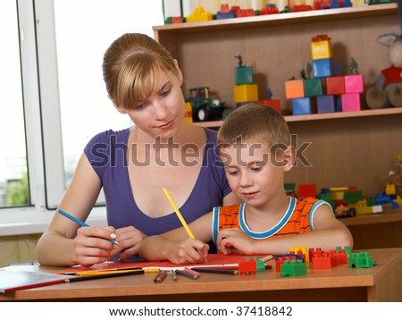 The mum with son is engaged in a children's room - stock photo