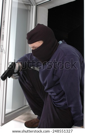 The murderer in the balaclava is entering with the handgun - stock photo