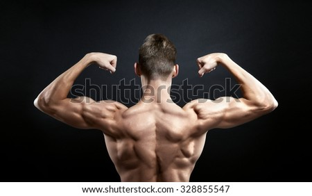 The muscular male back on black background - stock photo