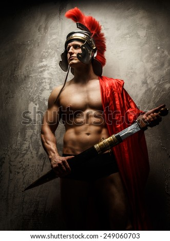 The muscular man in Roman armor holding sword. - stock photo