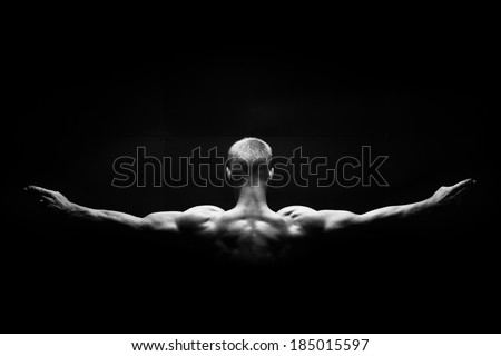 the muscular man's back  on black background - stock photo