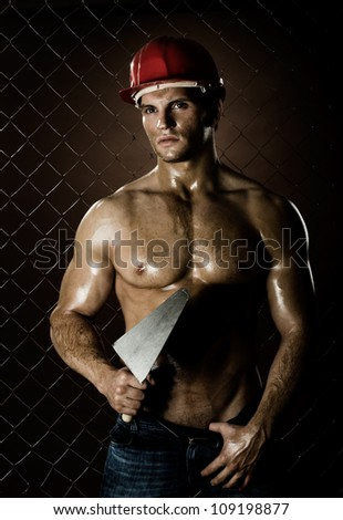 the  muscular worker  man, in  safety helmet  with trowel in hand, on netting fence background - stock photo