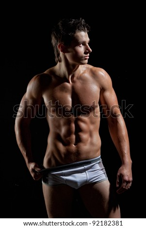 The muscular young naked sexy man takes off her underwear - stock photo