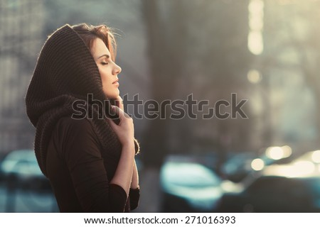 The mysterious pensive woman in a hood in the sunset city - stock photo