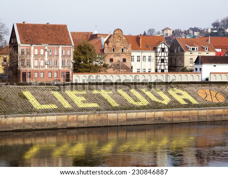 The name of the country Lithuania together with a basketball painted on the bank of Nemunas River in the city of Kaunas. - stock photo
