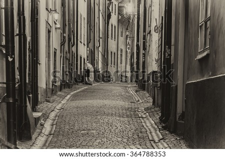 The narrow street of Gamla Stan - historic city old center of Stockholm, at summer night - black and white monochrome style - stock photo