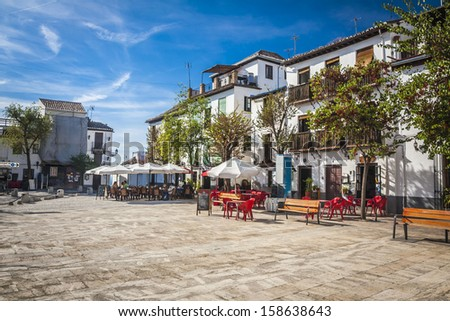 The narrow street with old houses, Granada, Spain. - stock photo