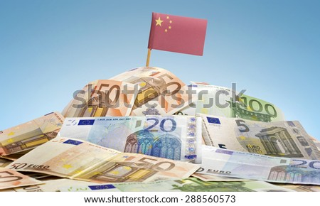 The national flag of China sticking in a pile of mixed european banknotes.(series) - stock photo