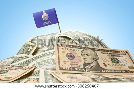 The national flag of Kansas sticking in a pile of american dollars.(series) - stock photo