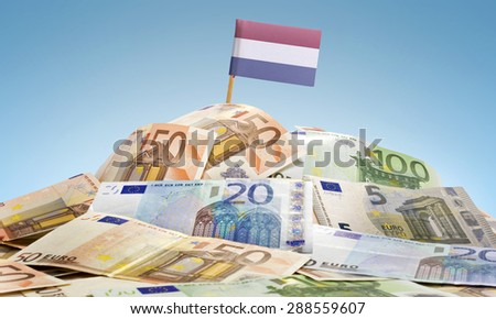 The national flag of Netherlands sticking in a pile of mixed european banknotes.(series) - stock photo