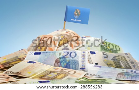 The national flag of Oklahoma sticking in a pile of mixed european banknotes.(series) - stock photo
