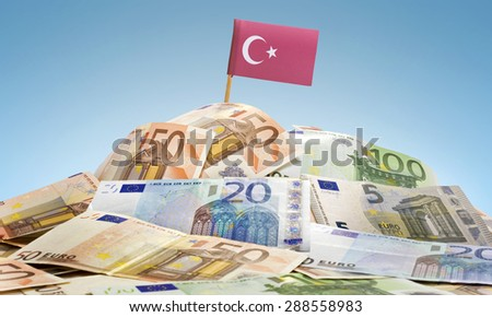 The national flag of Turkey sticking in a pile of mixed european banknotes.(series) - stock photo