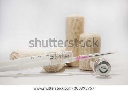 The needle with a syringe and medical bandage on the white background. - stock photo