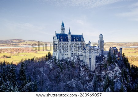 The Neuschwanstein Castle in winter on a rock, in the shadow of the mountains and snow-covered forest - stock photo