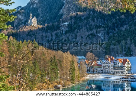 The Neuschwanstein castle overlooking the town of Hohenschwangau and lake Alpsee on a sunny winter day with snow and frost; Fussen, Bavaria, Germany - stock photo