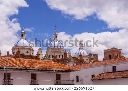 The New Cathedral or La Catedral de la Inmaculada Concepcion behind Spanish tiled roofs.  Cuenca, Ecuador. - stock photo