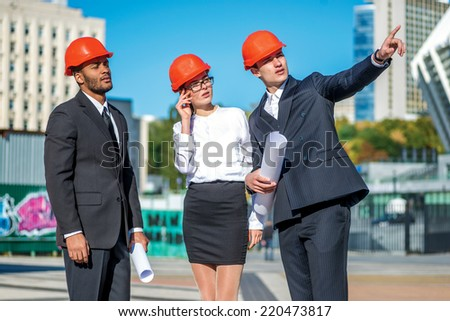 The new tasks for the construction. Three confident business architect in protective helmet standing on the site and keep the blueprints in his hands while considering the object and pointing - stock photo