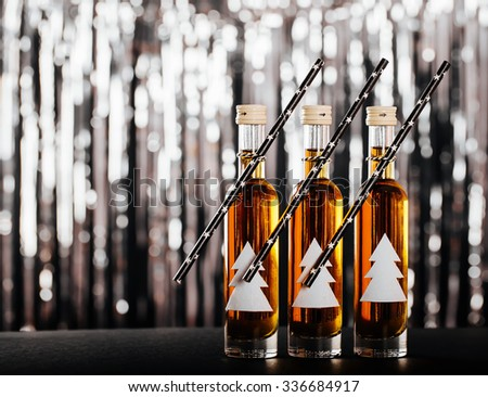 The New Year's Eve Bar. Decorated bottle with Christmas tree on blurred background with black shiny bokeh - stock photo