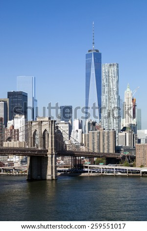 The New York City skyline at afternoon w the Freedom tower and Brooklyn bridge - stock photo