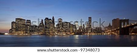 The New York City skyline at twilight w Brooklyn Bridge - stock photo