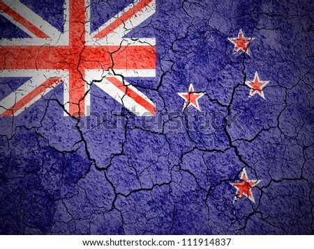 The New Zealand flag painted on  cracked ground with vignette - stock photo