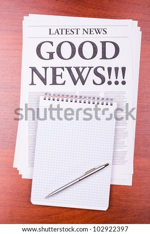 The newspaper LATEST NEWS with the headline GOOD NEWS!!! and notepad - stock photo