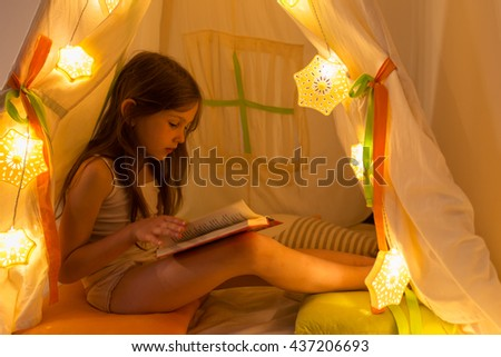 The night. Girl reading a book in the tent. Houses, before going to bed, bedside lamp - stock photo
