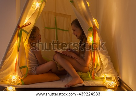 The night. Girls reading a book in the tent. Houses, before going to bed, bedside lamp - stock photo