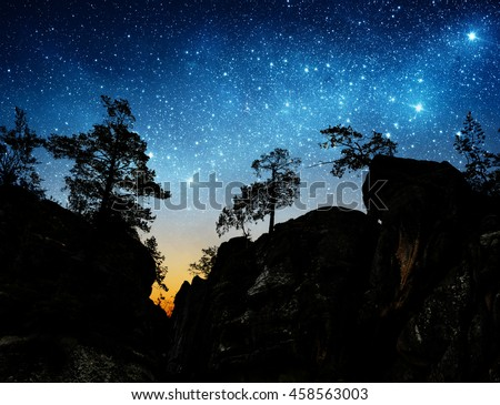 The night sky on the background of mountains and trees.  - stock photo